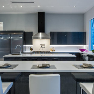 Large midcentury l-shaped open plan kitchen in Los Angeles with flat-panel cabinets, grey cabinets, marble benchtops, white splashback, stainless steel appliances and with island.