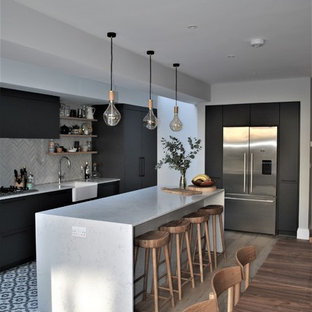 Inspiration for a contemporary kitchen/diner in London with a belfast sink, flat-panel cabinets, grey cabinets, quartz worktops, white splashback, metro tiled splashback, ceramic flooring and multi-coloured floors.