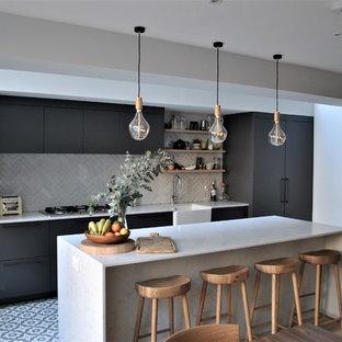 Moderne Wohnküche mit Landhausspüle, flächenbündigen Schrankfronten, grauen Schränken, Quarzit-Arbeitsplatte, Küchenrückwand in Weiß, Rückwand aus Metrofliesen, Keramikboden, buntem Boden, Küchengeräten aus Edelstahl, Kücheninsel und weißer Arbeitsplatte in London