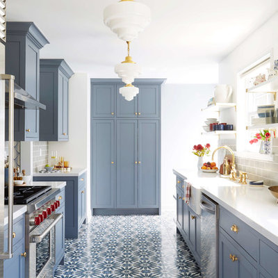 Example of a transitional l-shaped multicolored floor kitchen design in San Francisco with a farmhouse sink, shaker cabinets, blue cabinets, gray backsplash, subway tile backsplash and stainless steel appliances