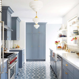 Transitional kitchen appliance - Example of a transitional galley multicolored floor kitchen design in San Francisco with a farmhouse sink, shaker cabinets, blue cabinets, gray backsplash, subway tile backsplash and stainless steel appliances