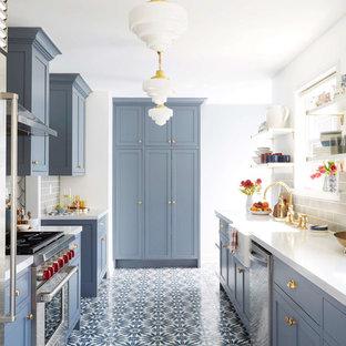 サンフランシスコのトランジショナルスタイルのおしゃれなII型キッチン (エプロンフロントシンク、シェーカースタイル扉のキャビネット、青いキャビネット、グレーのキッチンパネル、サブウェイタイルのキッチンパネル、シルバーの調理設備、マルチカラーの床) の写真
