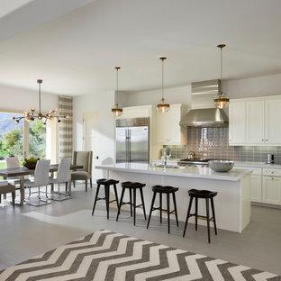 На фото: серо-белая угловая кухня-гостиная в стиле неоклассика (современная классика) с фасадами в стиле шейкер, белыми фасадами, серым фартуком, фартуком из плитки кабанчик, техникой из нержавеющей стали и островом с