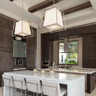 マイアミの広いモダンスタイルのおしゃれなキッチン (フラットパネル扉のキャビネット、濃色木目調キャビネット、パネルと同色の調理設備、白いキッチンカウンター、アンダーカウンターシンク、磁器タイルの床、ベージュの床) の写真