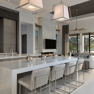 Large modern l-shaped kitchen in Miami with an undermount sink, flat-panel cabinets, dark wood cabinets, panelled appliances, porcelain floors, multiple islands, beige floor and white benchtop.