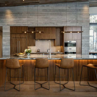 This is an example of a contemporary galley open plan kitchen in Salt Lake City with an undermount sink, flat-panel cabinets, dark wood cabinets, stainless steel appliances, dark hardwood floors, with island, brown floor, grey benchtop, vaulted and wood.