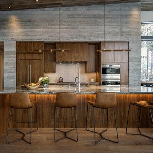 Стильный дизайн: параллельная кухня-гостиная в современном стиле с врезной раковиной, плоскими фасадами, темными деревянными фасадами, техникой из нержавеющей стали, темным паркетным полом, островом, коричневым полом, серой столешницей, сводчатым потолком и деревянным потолком - последний тренд