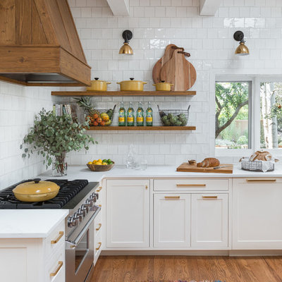 Example of a minimalist l-shaped medium tone wood floor open concept kitchen design in Albuquerque with a farmhouse sink, white cabinets, white backsplash, ceramic backsplash, stainless steel appliances, quartzite countertops, an island and shaker cabinets