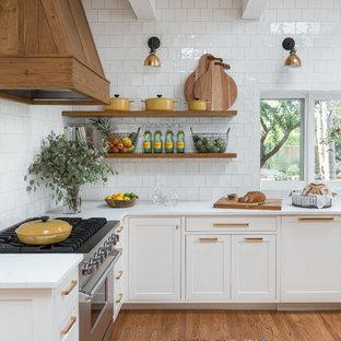 Modelo de cocina en L, minimalista, abierta, con fregadero sobremueble, armarios con paneles empotrados, puertas de armario blancas, salpicadero blanco, salpicadero de azulejos de cerámica, electrodomésticos de acero inoxidable, suelo de madera en tonos medios, encimera de cuarcita y una isla