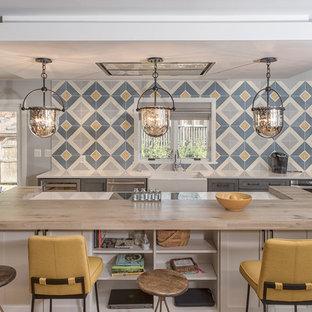 Modelo de cocina de estilo de casa de campo con fregadero sobremueble, armarios estilo shaker, puertas de armario grises, encimera de madera, salpicadero azul, salpicadero de azulejos de cerámica, suelo de madera clara y una isla