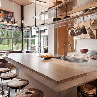 他の地域の大きいコンテンポラリースタイルのおしゃれなキッチン (アンダーカウンターシンク、フラットパネル扉のキャビネット、淡色木目調キャビネット、シルバーの調理設備の、淡色無垢フローリング、珪岩カウンター、メタリックのキッチンパネル、メタルタイルのキッチンパネル、ベージュの床、白いキッチンカウンター) の写真