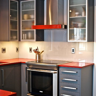 Contemporary u-shaped eat-in kitchen in Vancouver with an undermount sink, flat-panel cabinets, grey cabinets, quartz benchtops, grey splashback, glass sheet splashback, stainless steel appliances and red benchtop.