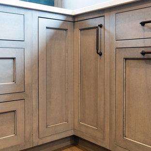 シカゴの広いカントリー風おしゃれなキッチン (シングルシンク、中間色木目調キャビネット、クオーツストーンカウンター、青いキッチンパネル、シルバーの調理設備、無垢フローリング、茶色い床、グレーのキッチンカウンター、落し込みパネル扉のキャビネット、セラミックタイルのキッチンパネル) の写真