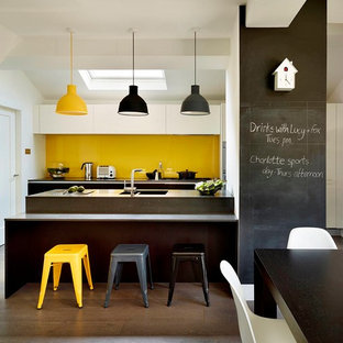 Mid-sized contemporary galley eat-in kitchen in Other with flat-panel cabinets, white cabinets, yellow splashback, dark hardwood floors, grey benchtop, a double-bowl sink, glass sheet splashback, a peninsula and brown floor.
