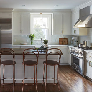 Mid-sized transitional kitchen pantry ideas - Mid-sized transitional u-shaped kitchen pantry photo in Chicago with shaker cabinets, white cabinets, marble countertops, white backsplash and an island