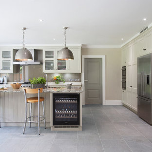 Design ideas for a classic kitchen in Surrey with recessed-panel cabinets, grey cabinets, grey splashback, glass sheet splashback, stainless steel appliances and an island.