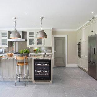 Idee per una cucina classica con ante con riquadro incassato, ante grigie, paraspruzzi grigio, paraspruzzi con lastra di vetro, elettrodomestici in acciaio inossidabile e isola