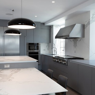 This is an example of a large contemporary l-shaped kitchen/diner in London with a built-in sink, flat-panel cabinets, grey cabinets, engineered stone countertops, white splashback, stone slab splashback, stainless steel appliances, ceramic flooring, an island, grey floors and white worktops.