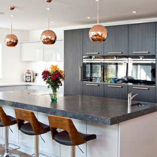 Photo of a large contemporary l-shaped kitchen in London with flat-panel cabinets, white splashback, medium hardwood flooring, an island, a submerged sink, white cabinets, black appliances and white worktops.