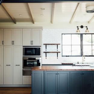 Imagen de cocina clásica renovada con armarios estilo shaker, salpicadero amarillo, electrodomésticos de acero inoxidable, suelo de madera clara y una isla