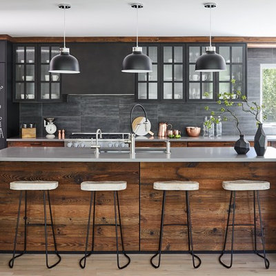 Inspiration for a mid-sized contemporary galley light wood floor and gray floor open concept kitchen remodel in New York with concrete countertops, stone tile backsplash, paneled appliances, an island, gray countertops, an undermount sink, medium tone wood cabinets, gray backsplash and glass-front cabinets
