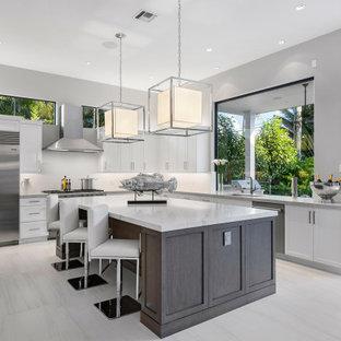 マイアミの広いコンテンポラリースタイルのおしゃれなキッチン (アンダーカウンターシンク、フラットパネル扉のキャビネット、淡色木目調キャビネット、クオーツストーンカウンター、白いキッチンパネル、クオーツストーンのキッチンパネル、シルバーの調理設備、磁器タイルの床、白い床、白いキッチンカウンター、格子天井) の写真