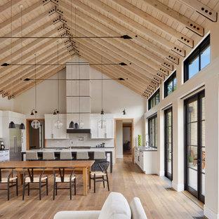 На фото: большая п-образная кухня-гостиная в стиле кантри с фасадами с утопленной филенкой, белыми фасадами, столешницей из бетона, белым фартуком, фартуком из керамической плитки, техникой из нержавеющей стали, паркетным полом среднего тона, коричневым полом, серой столешницей, островом и сводчатым потолком с