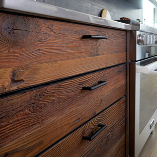 Design ideas for a large industrial galley eat-in kitchen in New York with an undermount sink, flat-panel cabinets, dark wood cabinets, grey splashback, black appliances, light hardwood floors, with island, beige floor and grey benchtop.