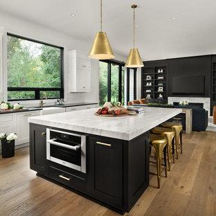 Geräumige Landhausstil Küche in U-Form mit Kücheninsel, Landhausspüle, Schrankfronten im Shaker-Stil, schwarzen Schränken, Küchenrückwand in Weiß, Küchengeräten aus Edelstahl, braunem Holzboden, braunem Boden und weißer Arbeitsplatte in Detroit