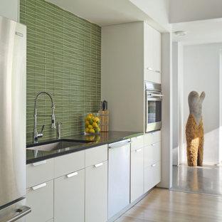 バーリントンの中サイズのカントリー風おしゃれなキッチン (シルバーの調理設備の、シングルシンク、フラットパネル扉のキャビネット、白いキャビネット、緑のキッチンパネル、御影石カウンター、モザイクタイルのキッチンパネル、淡色無垢フローリング) の写真