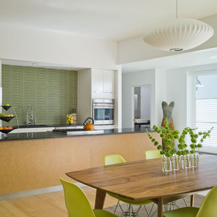 Design ideas for a mid-sized country galley eat-in kitchen in Burlington with stainless steel appliances, flat-panel cabinets, white cabinets, green splashback, a single-bowl sink, granite benchtops, mosaic tile splashback, light hardwood floors and with island.