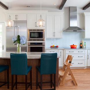 Exemple d'une grand cuisine américaine parallèle moderne avec un îlot central, un placard à porte shaker, des portes de placard blanches, une crédence en carreau de verre, un électroménager en acier inoxydable, un plan de travail en granite, un sol marron, un sol en bois brun, un évier de ferme et une crédence bleue.