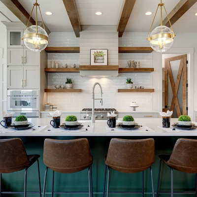 Open concept kitchen - large farmhouse l-shaped light wood floor and beige floor open concept kitchen idea in Boise with a farmhouse sink, shaker cabinets, white backsplash, subway tile backsplash, stainless steel appliances, an island, white countertops, white cabinets and quartz countertops