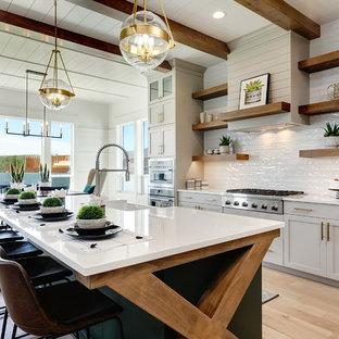 ボイシの大きいカントリー風おしゃれなキッチン (エプロンフロントシンク、シェーカースタイル扉のキャビネット、白いキャビネット、クオーツストーンカウンター、白いキッチンパネル、サブウェイタイルのキッチンパネル、シルバーの調理設備の、淡色無垢フローリング、ベージュの床、白いキッチンカウンター) の写真
