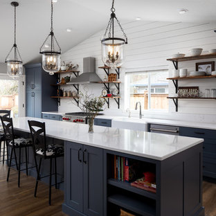 Exemple d'une grande cuisine ouverte parallèle nature avec un évier de ferme, un placard à porte shaker, des portes de placard bleues, un plan de travail en quartz modifié, une crédence blanche, une crédence en bois, un électroménager en acier inoxydable, un sol en vinyl, un îlot central et un sol marron.