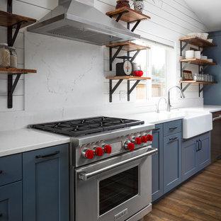 Idée de décoration pour une grande cuisine ouverte parallèle champêtre avec un évier de ferme, un placard à porte shaker, des portes de placard bleues, un plan de travail en quartz modifié, une crédence blanche, une crédence en bois, un électroménager en acier inoxydable, un sol en vinyl, un îlot central et un sol marron.