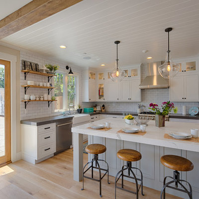 Inspiration for a large country l-shaped medium tone wood floor and brown floor enclosed kitchen remodel in San Francisco with a farmhouse sink, shaker cabinets, white cabinets, white backsplash, subway tile backsplash, stainless steel appliances, an island and quartzite countertops