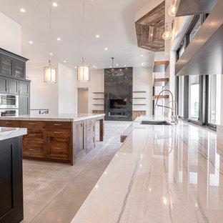 ソルトレイクシティの大きいカントリー風おしゃれなキッチン (アンダーカウンターシンク、ガラス扉のキャビネット、黒いキャビネット、珪岩カウンター、ベージュキッチンパネル、石スラブのキッチンパネル、シルバーの調理設備の、コンクリートの床、グレーの床、ベージュのキッチンカウンター) の写真