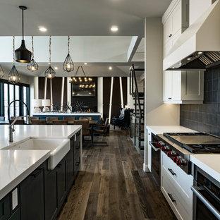エドモントンの巨大なインダストリアルスタイルのおしゃれなキッチン (エプロンフロントシンク、シェーカースタイル扉のキャビネット、白いキャビネット、クオーツストーンカウンター、黒いキッチンパネル、メタルタイルのキッチンパネル、シルバーの調理設備の、無垢フローリング、茶色い床) の写真
