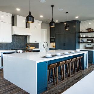 エドモントンの巨大なインダストリアルスタイルのおしゃれなキッチン (エプロンフロントシンク、シェーカースタイル扉のキャビネット、青いキャビネット、クオーツストーンカウンター、マルチカラーのキッチンパネル、メタルタイルのキッチンパネル、シルバーの調理設備の、無垢フローリング、茶色い床) の写真