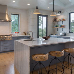 Large farmhouse eat-in kitchen inspiration - Eat-in kitchen - large cottage u-shaped light wood floor eat-in kitchen idea in New York with a farmhouse sink, blue cabinets, granite countertops, white backsplash, ceramic backsplash, stainless steel appliances, an island and shaker cabinets