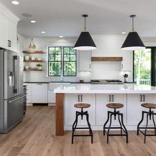他の地域のカントリー風おしゃれなキッチン (エプロンフロントシンク、シェーカースタイル扉のキャビネット、白いキャビネット、白いキッチンパネル、サブウェイタイルのキッチンパネル、シルバーの調理設備の、無垢フローリング、ベージュの床、白いキッチンカウンター) の写真
