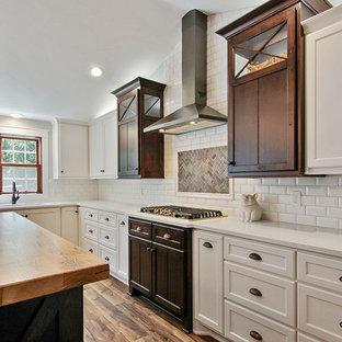 他の地域のカントリー風おしゃれなアイランドキッチン (アンダーカウンターシンク、フラットパネル扉のキャビネット、白いキャビネット、クオーツストーンカウンター、黄色いキッチンパネル、セラミックタイルのキッチンパネル、シルバーの調理設備、クッションフロア、茶色い床) の写真