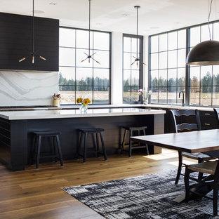 Foto på ett stort funkis vit kök, med en undermonterad diskho, luckor med infälld panel, svarta skåp, marmorbänkskiva, vitt stänkskydd, stänkskydd i marmor, rostfria vitvaror, mellanmörkt trägolv, en köksö och brunt golv