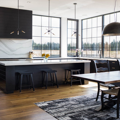 Example of a large trendy medium tone wood floor and brown floor eat-in kitchen design in Seattle with an undermount sink, recessed-panel cabinets, black cabinets, marble countertops, white backsplash, marble backsplash, stainless steel appliances, an island and white countertops