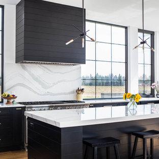 シアトルの大きいモダンスタイルのおしゃれなキッチン (アンダーカウンターシンク、落し込みパネル扉のキャビネット、黒いキャビネット、大理石カウンター、白いキッチンパネル、大理石のキッチンパネル、シルバーの調理設備、無垢フローリング、白いキッチンカウンター) の写真