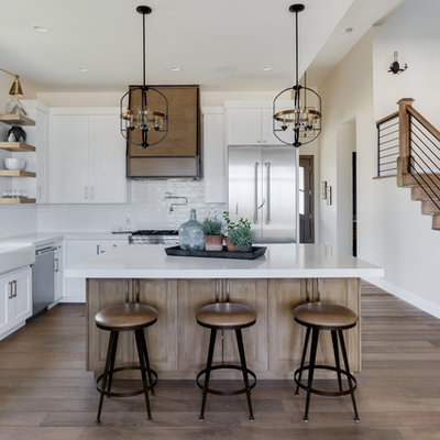 Example of a farmhouse l-shaped light wood floor kitchen design in Salt Lake City with a farmhouse sink, shaker cabinets, white cabinets, white backsplash, subway tile backsplash, stainless steel appliances, an island, white countertops and quartzite countertops