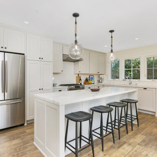 Photo of a mid-sized country l-shaped open plan kitchen in San Diego with an undermount sink, flat-panel cabinets, grey cabinets, quartz benchtops, white splashback, subway tile splashback, stainless steel appliances, vinyl floors, with island, brown floor and white benchtop.