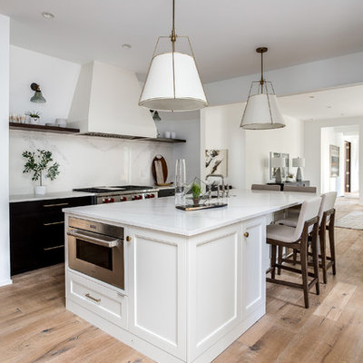 Inspiration for a large cottage galley light wood floor and brown floor kitchen remodel in Denver with a farmhouse sink, shaker cabinets, white cabinets, marble countertops, white backsplash, marble backsplash, stainless steel appliances, an island and white countertops
