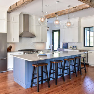 Mid-sized cottage l-shaped medium tone wood floor and brown floor open concept kitchen photo in Other with a farmhouse sink, shaker cabinets, white cabinets, quartz countertops, white backsplash, cement tile backsplash, stainless steel appliances, an island and gray countertops